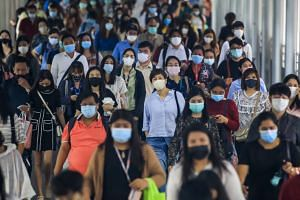Commuters wearing protective masks walk through an overpass in Bangkok on Sept 1, 2020.