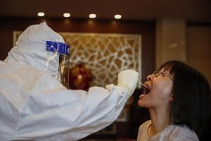 A medical worker swabs the throat of a journalist at a hotel in Beijing on Sept 7, 2020.