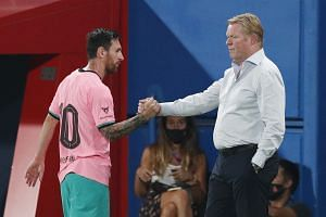 Barcelona's Lionel Messi shakes hands with coach Ronald Koeman as he is substituted off.
