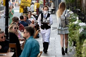 A waiter serves customers at tables outside a restaurant in London's Soho on Sept 20, 2020.