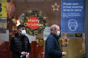People walk past the window of a closed shop displaying Christmas decorations in the centre of Manchester, on Nov 26, 2020.