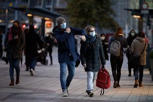 People wearing protective face masks walk on the street in Geneva.