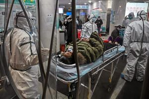 Medical staff wearing protective clothing arriving with a patient at the Wuhan Red Cross Hospital in Wuhan on Jan 25, 2020.