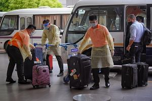 Attendants at Changi Airport's Terminal 3 handling luggage belonging to passengers from a flight which arrived from London yesterday, as the passengers boarded buses that would take them to dedicated facilities to serve their stay-home notice.