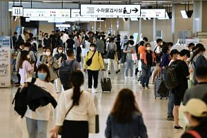 Travellers arrive at the departure hall of Gimpo airport in Seoul on Sept 29, 2020.