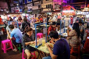 Diners separated by screen dividers at a street food corner in Bangkok on Sunday. Thailand, battling its second wave of coronavirus infections, has imposed an array of restrictions that vary depending on which provincial border one crosses, with the