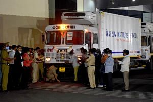 A police officer performs prayers in front of a truck carrying the first consignment of Covishield, in Pune, India, on Jan 12, 2021.