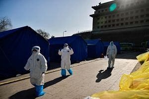Medical staff walk at a nucleic acid testing site in Beijing, on Jan 18, 2021.