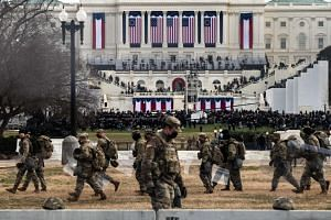 US National Guard troops carry riot shields as they assume positions in the vicinity of the US Capitol as the Inauguration of US President-Elect Joe Biden begins in Washington.