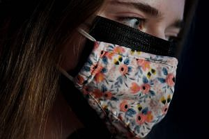 AN illustration shows a woman wearing two face masks, a cloth mask over a surgical mask.