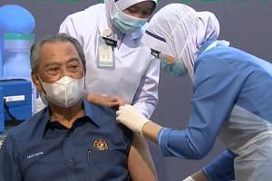 Malaysia's Prime Minister Muhyiddin Yassin receiving the first of the two-dose Pfizer-BioNTech vaccine at a public clinic in Putrajaya.
