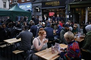 Customers enjoy drinks at tables outside the bars in the Soho area of London, on April 12, 2021.