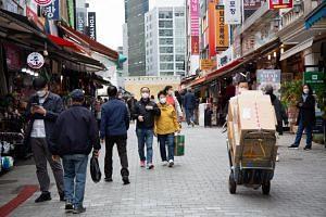People wearing face masks walk around Namdaemun market in Seoul, South Korea, on April 12, 2021.