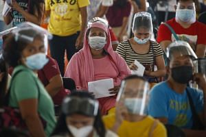 Filipinos queue to receive financial assistance as part of a relief programme for families affected by Covid-19 lockdown measures in Marikina City, Metro Manila, on April 13, 2021.
