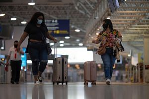 Travellers walk near the boarding area at the Galeao International airport in Rio de Janeiro, on April 13, 2021.