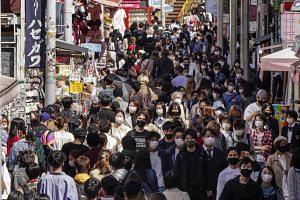 People wearing protective masks swarm the Takeshita Street at Harajuku in Tokyo, on April 18, 2021.