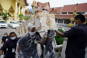 Temple workers carry a coffin containing the body of a man who died from Covid-19 during his funeral at a temple in Bangkok, on April 24, 2021.
