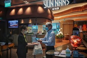Restaurant manager Ken Lim passing an order to a customer at Yun Nans restaurant at Westgate mall on May 5, 2021.