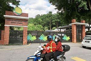 A motorcyclist riding past Taman Persekutuan Bukit Kiara in Kuala Lumpur, which has been closed under the latest MCO.