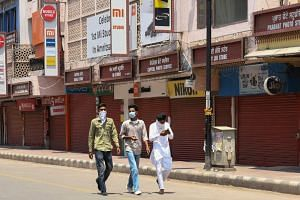 People walk past closed shops in a market area in Amritsar, India, on May 8, 2021.