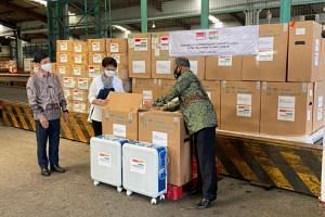 Indonesian Foreign Minister Retno Marsudi (centre) flagged off a consignment of oxygen tanks to India at Soekarno-Hatta airport on May 12, 2021.