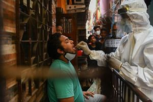 In a photo from March 11, 2021, a resident is swabbed for a sample at Dharavi slum in Mumbai.