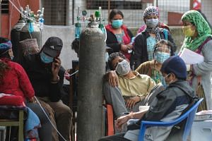 Covid-19 patients breathe with the help of medical oxygen outside an emergency ward in Kathmandu, on May 13, 2021.