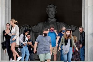Tourists, some in face masks while others are not, visit the Lincoln Memorial in Washington DC, on May 14, 2021.
