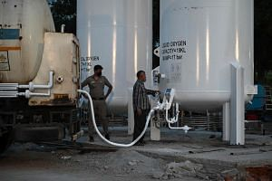 Workers load oxygen into newly installed tanks to be used for Covid-19 patients in New Delhi on May 12, 2021.