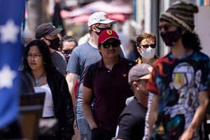 People walk down a street in Encinitas, California, on May 17, 2021.