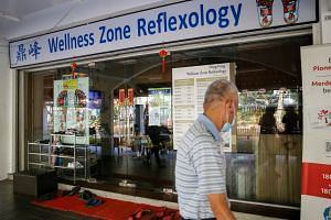 Ding Feng Wellness Zone Reflexology at Block 684 Hougang Ave 8 has seen a 70 per cent drop in footfall since Covid-19 cases were detected at the nearby Block 506, says Madam Goh Ai Kim, a massage therapist who works at the foot reflexology shop.