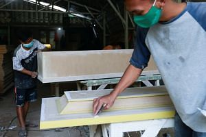 Workers prepare coffins ordered for Covid-19 victims at a workshop in South Tangerang, on the outskirts of Jakarta.