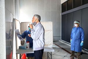 Prime Minister Lee Hsien Loong taking a Covid-19 breathalyser test before attending Parliament yesterday. The TracieX breathalyser test was developed locally by Silver Factory Technology, a start-up from Nanyang Technological University. PM Lee descr