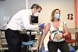 Health Minister Olivier Veran, who is a doctor by profession, delivers the vaccine shot to junior economy minister Olivia Gregoire.