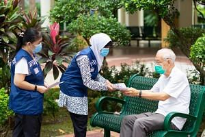 Madam Hamida Khalid (centre) was lauded for volunteering with the Singapore Police Force for 54 years.