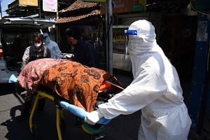 Health workers remove the body of a Covid-19 victim who died while isolating at home in Bandung, Indonesia, on July 28, 2021.