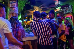 Masked and unmasked revellers at a bar in New Orleans, Louisiana, on July 23, 2021.