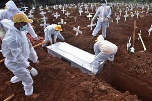 In this photo taken on Aug 6, 2021, grave diggers bury the coffin of Covid-19 victim at a cemetary in Bekasi, Indonesia.