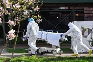 Medical personnel wearing protective equipment transport the body of a deceased patient in Brooklyn, New York, in 2020.