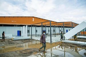 Labourers construct a Covid-19 quarantine centre with building materials from China in the border town of Muse on Sept 3, 2021.