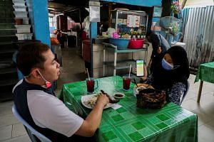 A diner showing her digital vaccination certificate at a restaurant in Kuala Lumpur on Aug 20, 2021.
