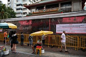 People praying outside the Kwan Im Thong Hood Cho Temple Waterloo Street on Sept 27, 2021. The latest Covid-19 restrictions aim to slow the pace at which cases are rising.