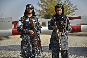 Taliban fighters working as policemen guard the entrance gate of a police district in Kabul on Oct 3, 2021.