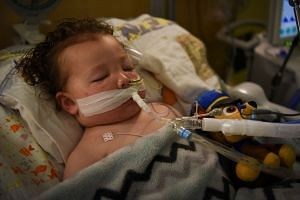 Adrian James, two, who tested positive for Covid-19, breathes with the help of a ventilator at a hospital in St Louis, Missouri.