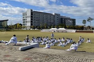 Afghan teenagers and children attending a taekwondo lesson held in a field at a state-run facility in Jincheon on Oct 13, 2021.