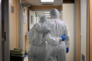 Health care workers wearing protective gear react at the end of their shift in a corridor of the level intensive care unit at the San Filippo Neri hospital in Rome.
