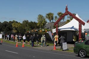 People queue outside a Covid-19 vaccination centre set up at a Maori meeting house and community centre in Auckland on Oct 16, 2021.
