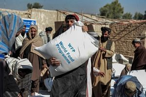 People carry grain sacks distributed by the World Food Programme in Kandahar on Oct 19, 2021.