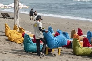 A man sets up seaters at a beach in Canggu, Bali, on Oct 22, after Indonesia reopened the tourist island for some international travellers.