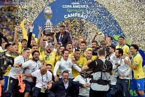 The Brazilian team celebrates with the Copa America trophy after defeating Peru in the final.